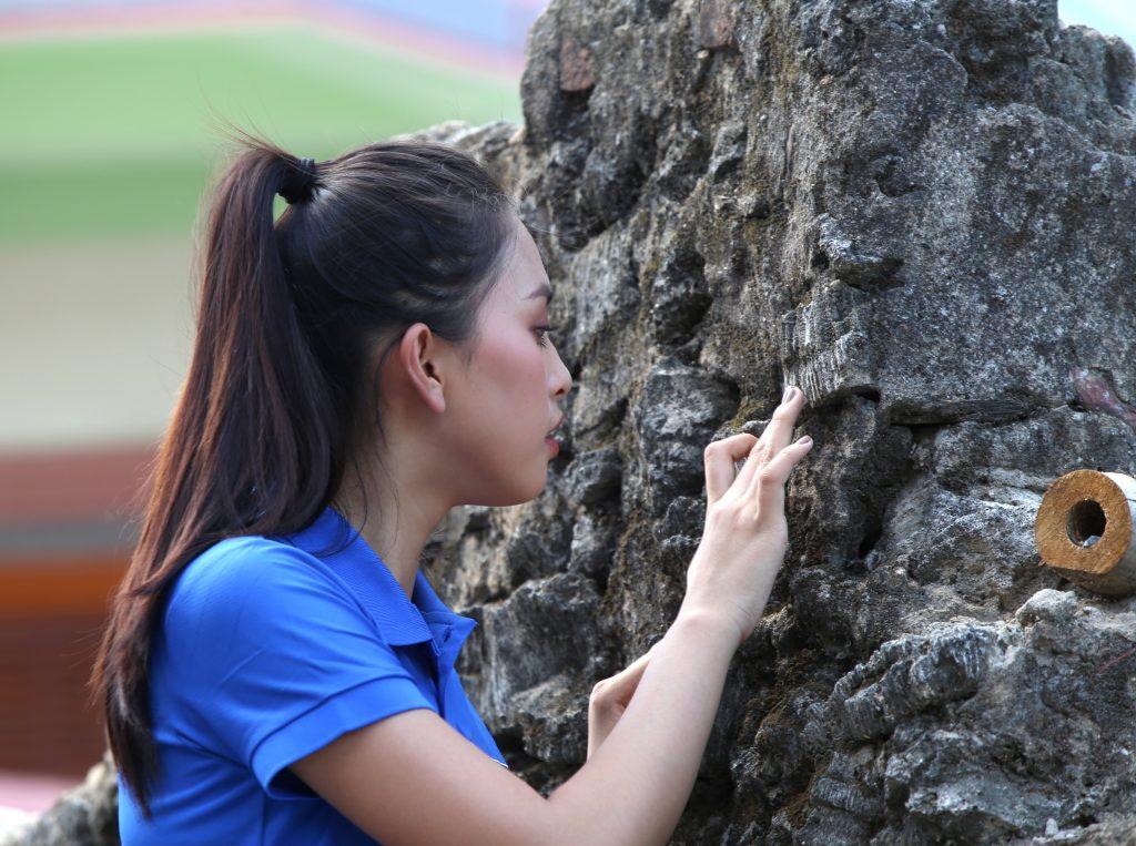 Hoa hậu Tiểu Vy quan sát tỷ mĩ bức tường rào lâu đời của làng Cảnh Dương